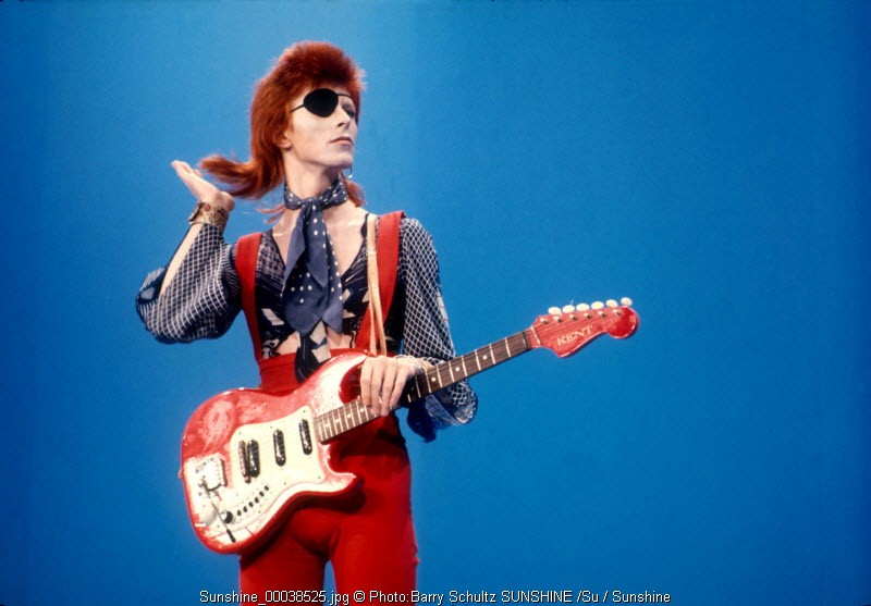David Bowie wears an eyepatch in red suit and guitar on blue background at Top Pop television studios in Holland while doing playback to his hit