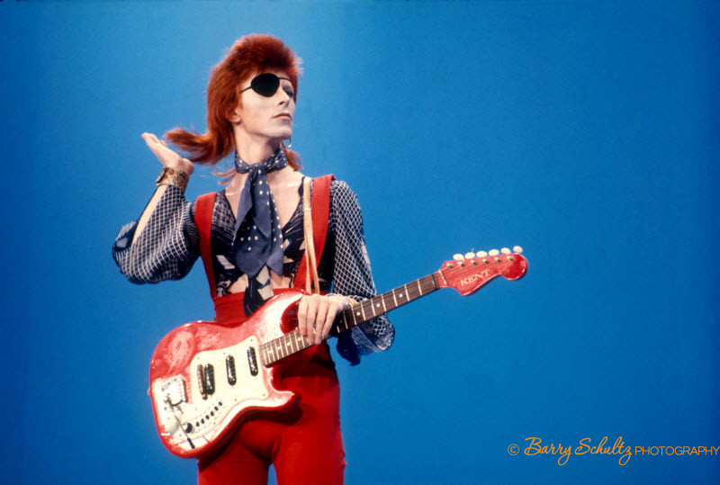 David Bowie wears an eyepatch in red suit and guitar on blue background at Top Pop television studios in Holland while doing playback to his hitdavid bowie, barry schultz, holland, netherlands, 1970, 70s, ziggy, stardust, retro, old school